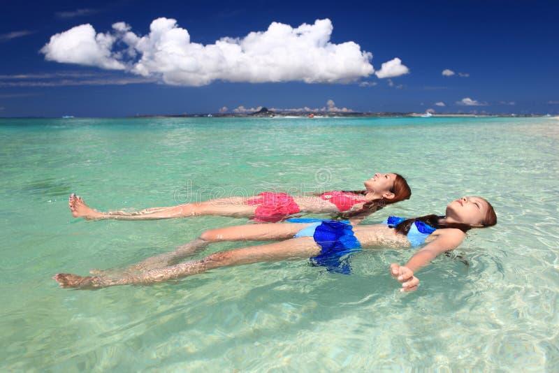 Mujeres jovenes que nadan en la playa imagen de archivo libre de regalías