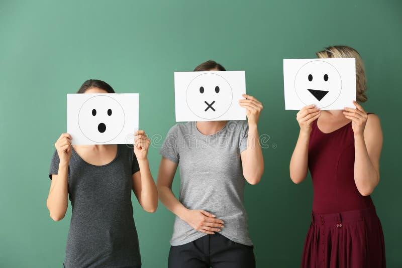 Mujeres jovenes que ocultan caras detrás de las hojas de papel con los emoticons exhaustos en fondo del color imagen de archivo libre de regalías