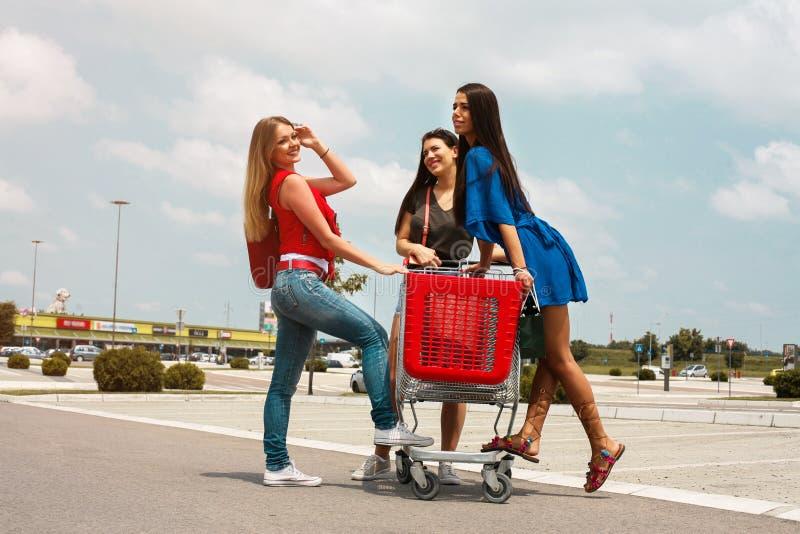 Mujeres jovenes que se divierten en un carro de la compra en la ciudad fotografía de archivo libre de regalías