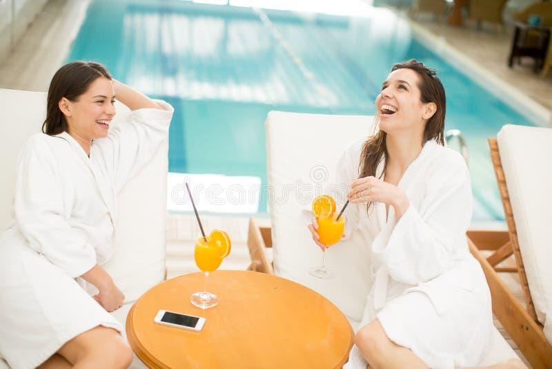 Mujeres jovenes que se relajan por la piscina imagen de archivo libre de regalías