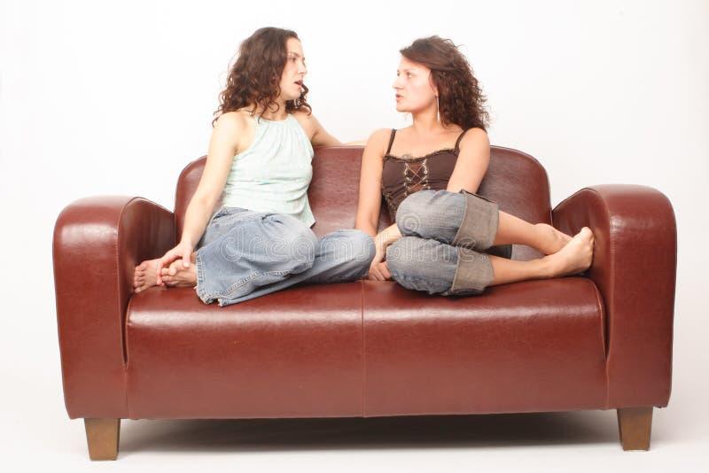 Mujeres jovenes que se sientan en el sofá y hablar fotografía de archivo