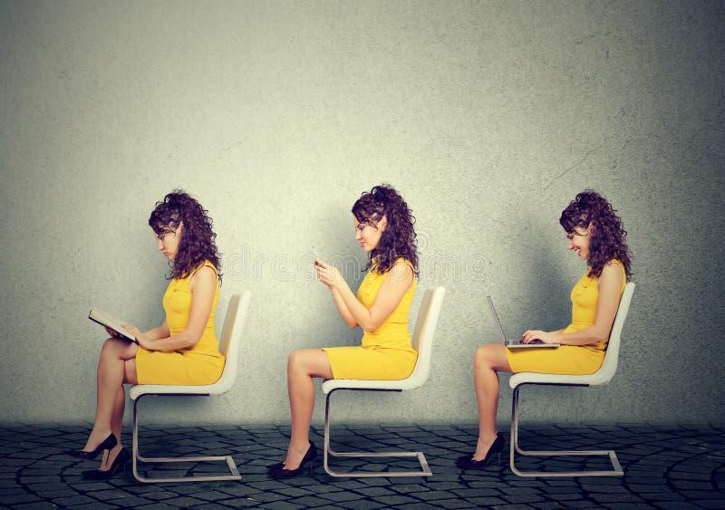 Mujeres jovenes que se sientan en la silla que lee un libro, mandando un SMS en el teléfono móvil usando el ordenador portátil imagen de archivo
