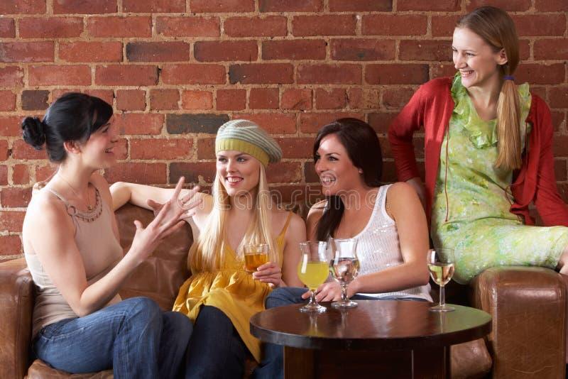 Mujeres jovenes que se sientan junto y que hablan fotos de archivo