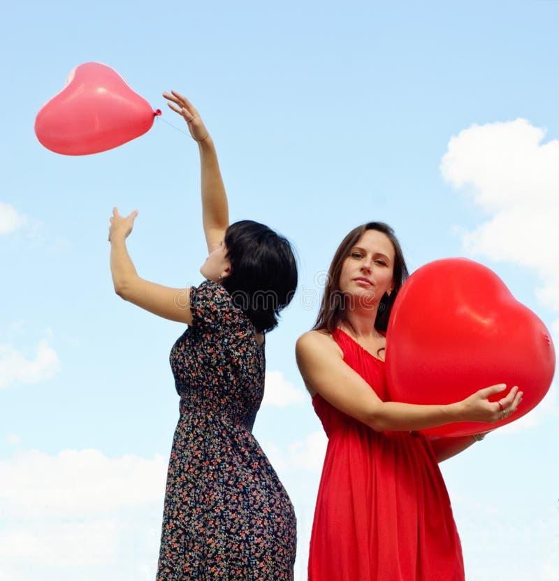Mujeres jovenes que sostienen los globos rojos contra el cielo imagenes de archivo