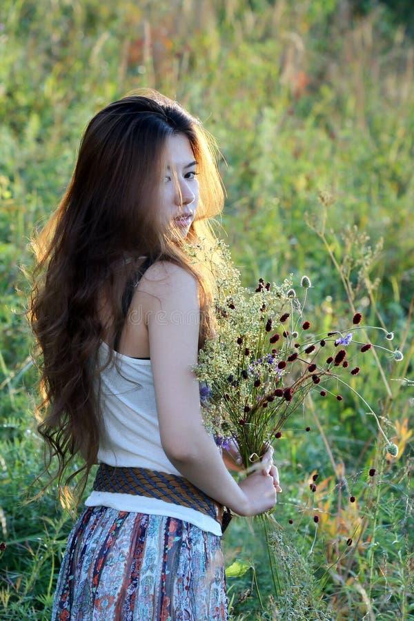 Mujeres jovenes que sostienen wildflowers fotos de archivo libres de regalías