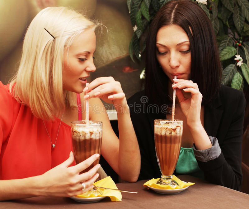 Mujeres jovenes que tienen descanso para tomar café junto imagen de archivo libre de regalías