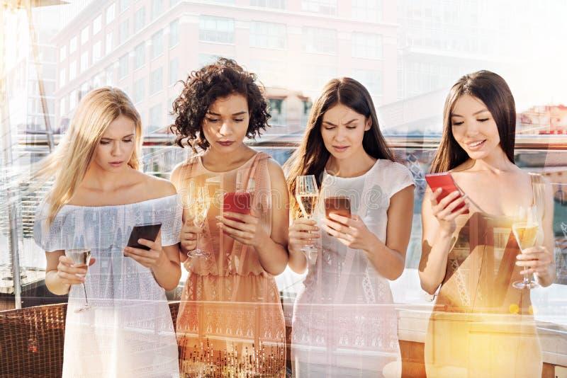 Mujeres jovenes serias que miran sus pantallas del smartphone imagenes de archivo