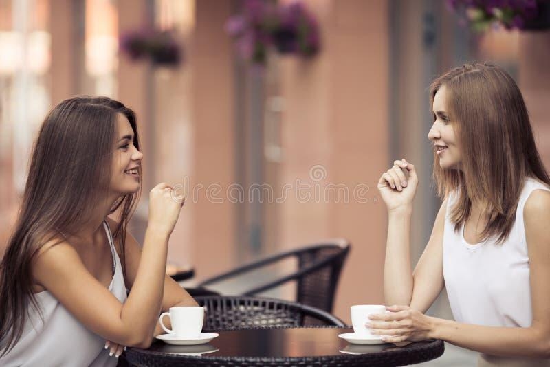 Mujeres jovenes sonrientes que beben el café imagen de archivo