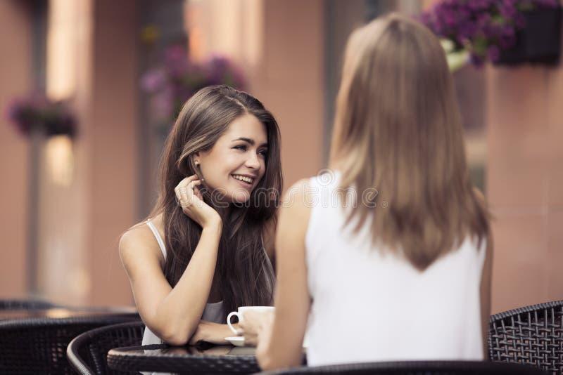 Mujeres jovenes sonrientes que beben el café imágenes de archivo libres de regalías