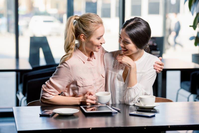 Mujeres jovenes sonrientes que usan la tableta digital mientras que bebe el café en café imagenes de archivo