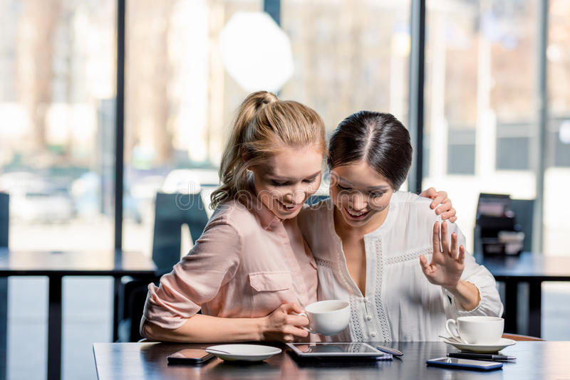 Mujeres jovenes sonrientes que usan la tableta digital mientras que bebe el café en café imagen de archivo