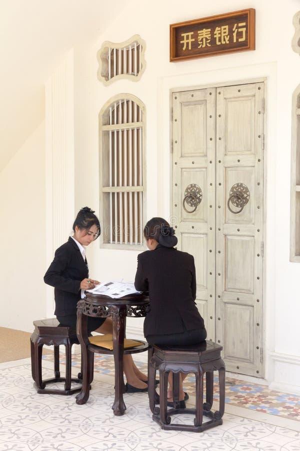 Mujeres jovenes tailandesas que se sientan en los muebles del estilo chino en la ciudad de Phuket, Tailandia imágenes de archivo libres de regalías