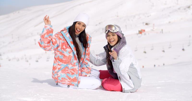 Mujeres jovenes vivaces de risa en nieve foto de archivo