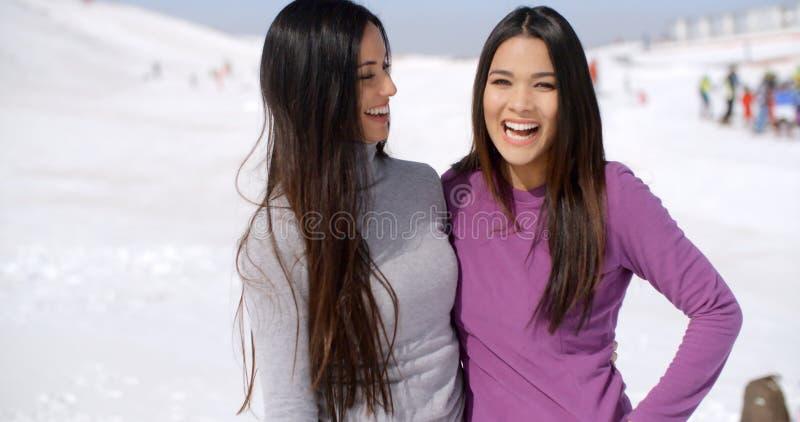 Mujeres jovenes vivaces de risa en una estación de esquí imágenes de archivo libres de regalías