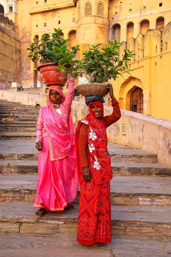 Mujeres locales que llevan los potes con las plantas en sus cabezas en Amber Fo foto de archivo