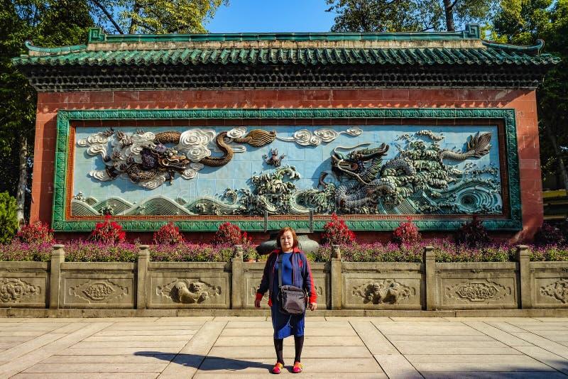 Mujeres mayores asiáticas con el dragón chino dos en la pared azul en 'el templo ancestral ' foto de archivo libre de regalías