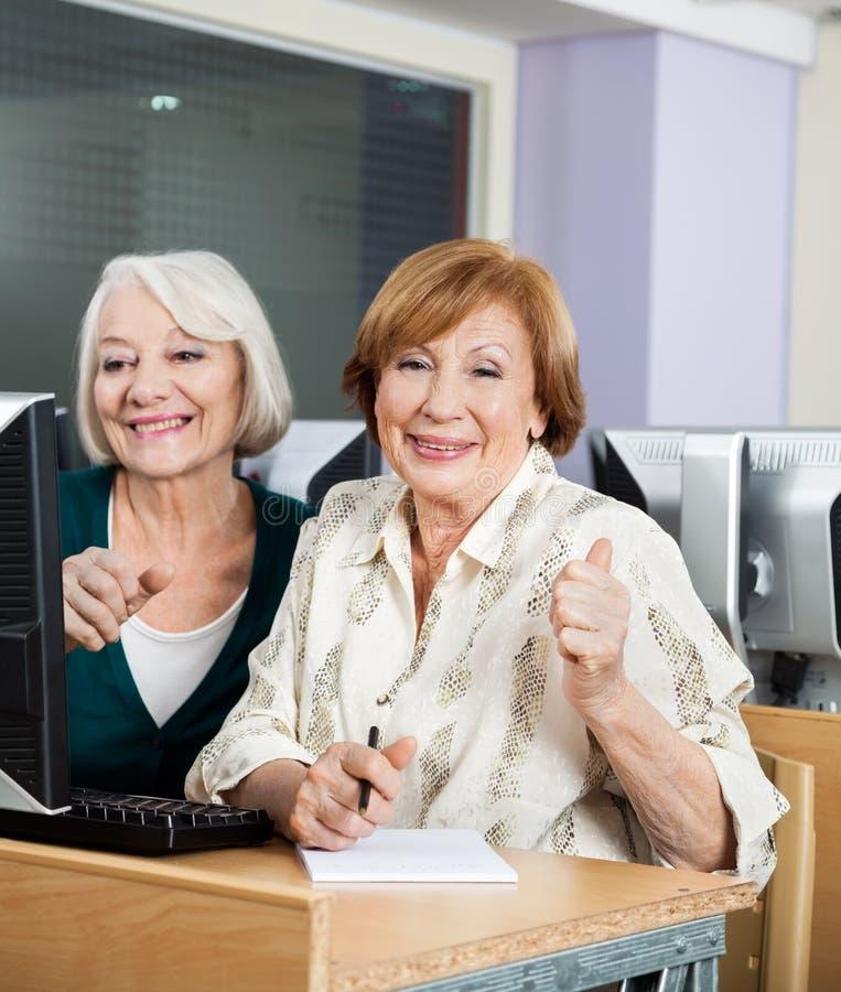 Mujeres mayores felices en el escritorio del ordenador en sala de clase foto de archivo libre de regalías