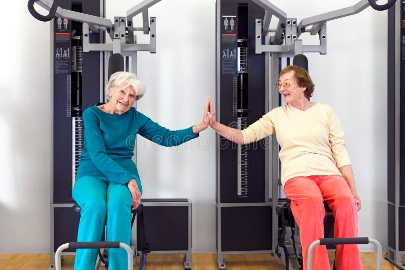 Mujeres mayores felices en el gimnasio que toca por las palmas foto de archivo