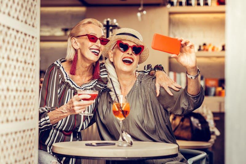 Mujeres mayores que llevan los equipos de moda mientras que fotograf?a fotografía de archivo libre de regalías