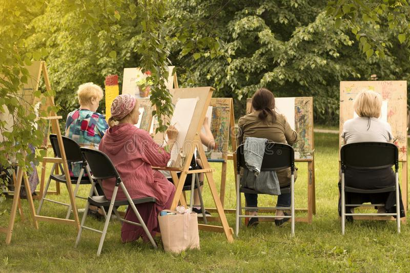 Mujeres mayores que pintan en el estudio de la escuela de arte para las personas mayores imagen de archivo libre de regalías
