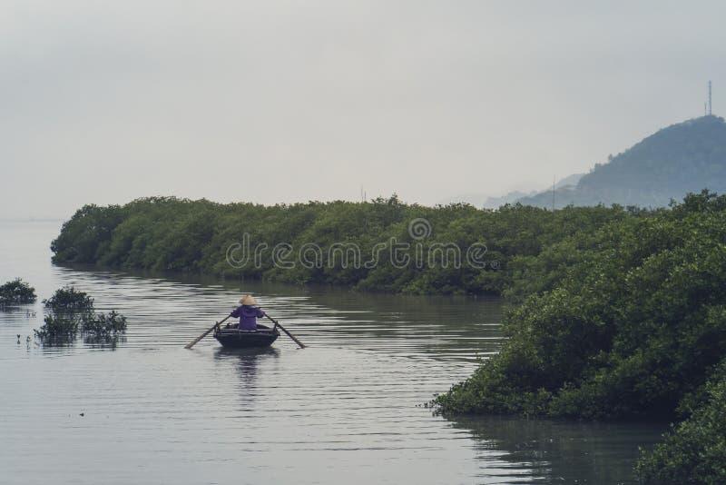 Mujeres mayores vietnamitas en el barco tradicional que se baten por el agua marr?n amarilla en canal fotos de archivo