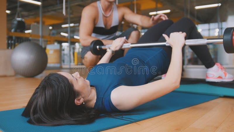 Mujeres morenas atractivas jovenes que hacen el ejercicio para las nalgas - la subida de un cuerpo que miente sobre la barra fotos de archivo