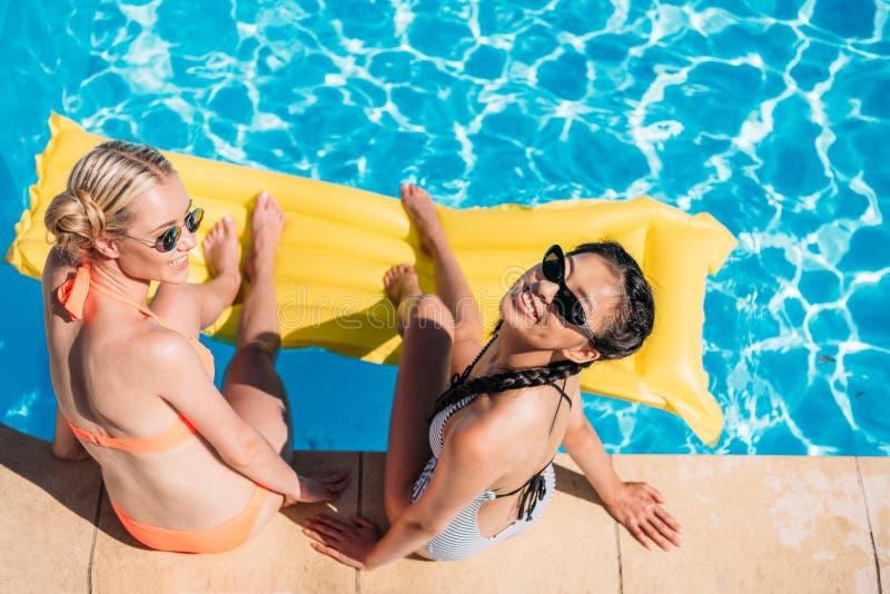 Mujeres multiétnicas hermosas jovenes que se sientan cerca de piscina foto de archivo