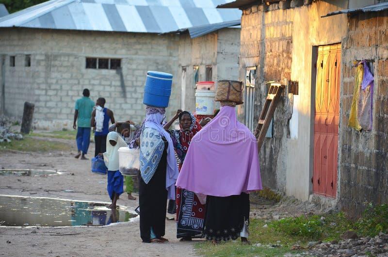 Mujeres musulmanes que llevan el agua en el pueblo, Zanzíbar imagenes de archivo