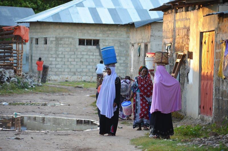 Mujeres musulmanes que llevan el agua en Zanzíbar fotos de archivo libres de regalías