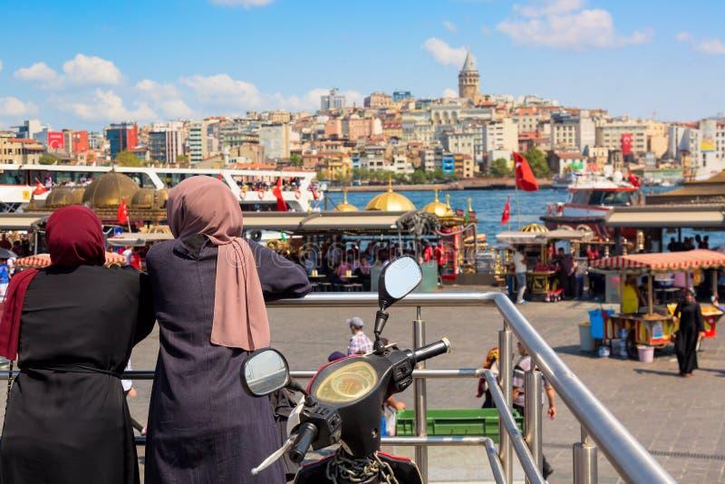 Mujeres musulmanes que miran el panorama de Estambul con la torre de Galata durante día soleado del verano Estambul, Turquía foto de archivo libre de regalías