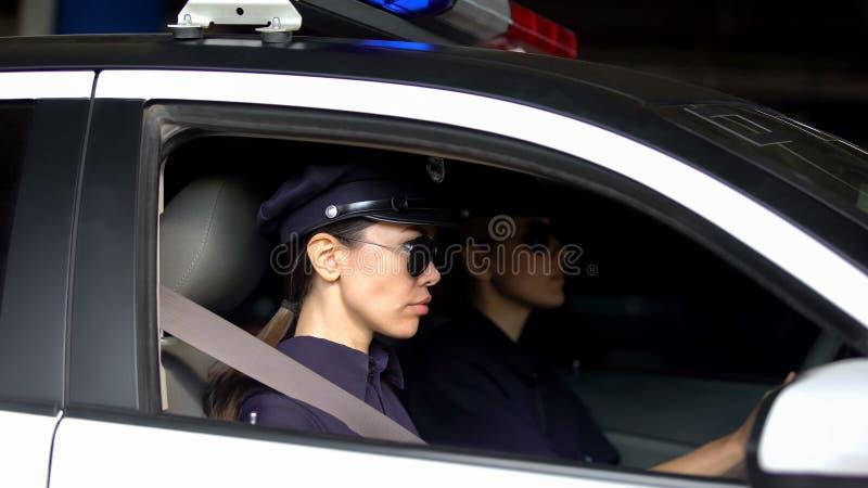 Mujeres policía serias que conducen el coche, leyes el patrullar del tráfico, supervisando orden foto de archivo libre de regalías