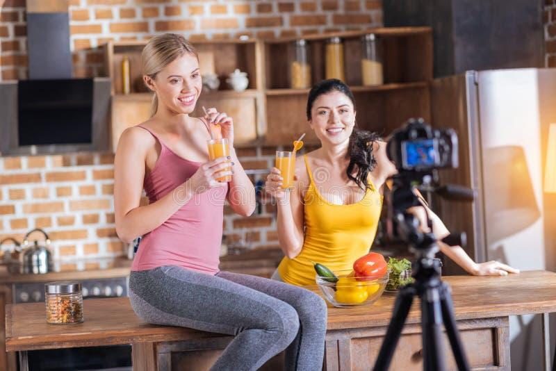 Mujeres positivas alegres que gozan del zumo de naranja foto de archivo