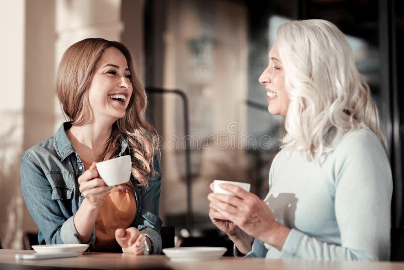 Mujeres positivas de diversa edad que ríen en un café junto fotografía de archivo libre de regalías