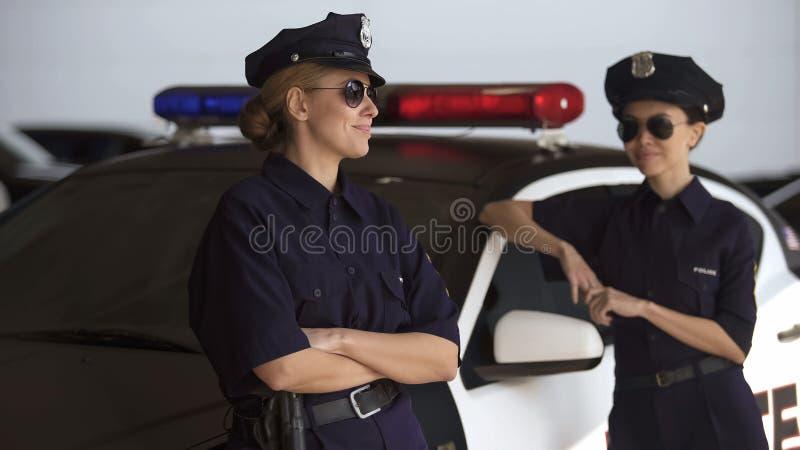 Mujeres positivas de la policía que se colocan cerca del coche, hablando y sonriendo, rotura del trabajo fotos de archivo libres de regalías