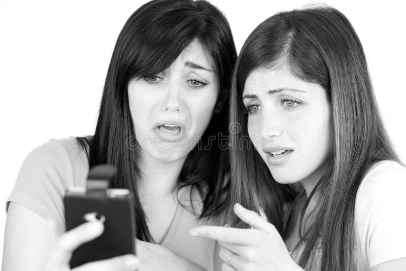 Mujeres preocupantes y horrorizadas por el mensaje de texto del matón en smartphone imagenes de archivo