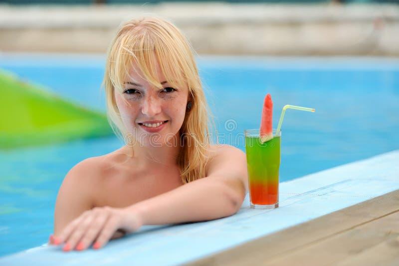 Mujeres que beben el cóctel en piscina foto de archivo