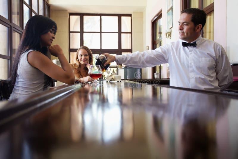 Mujeres que beben el coctel en pub foto de archivo
