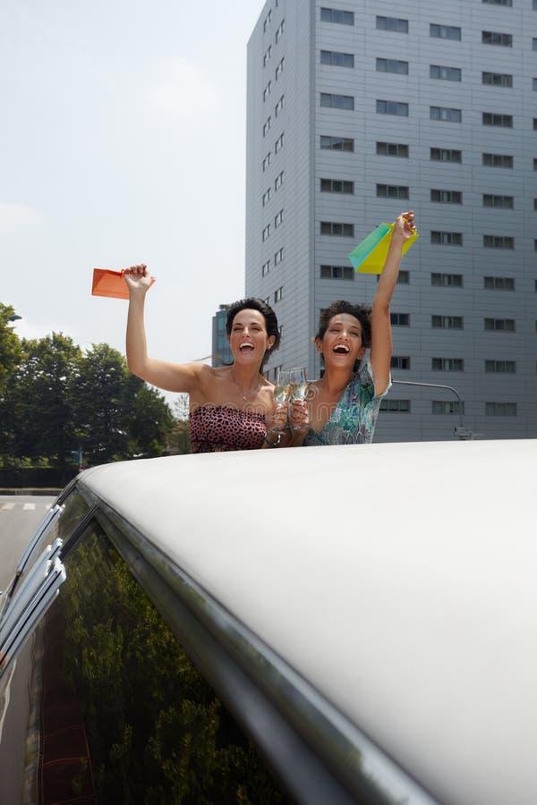 Mujeres que beben el vino en limusina fotos de archivo