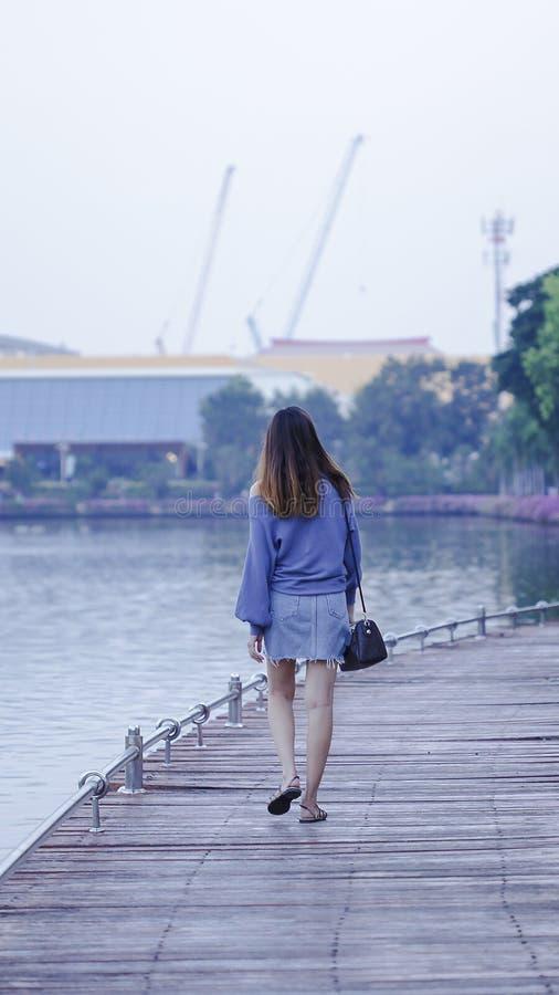 Mujeres que caminan en los puentes de madera imagenes de archivo