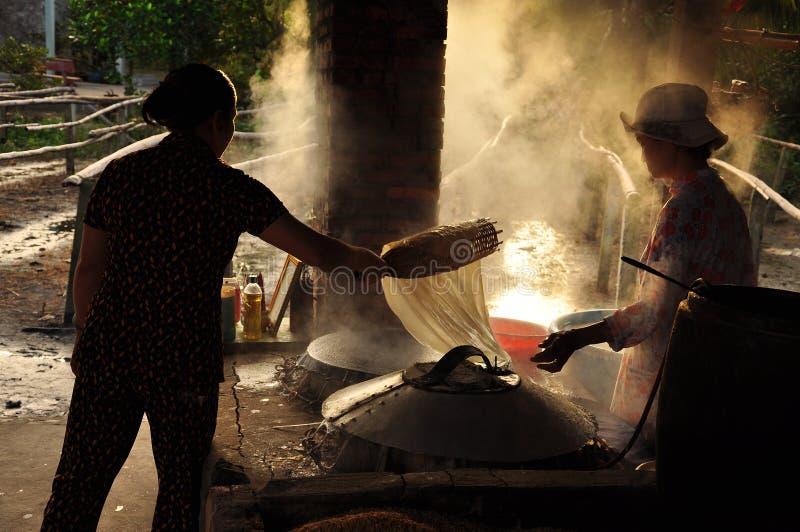 Mujeres que cocinan la goma del arroz para hacer los tallarines de arroz, Vietnam imagen de archivo libre de regalías