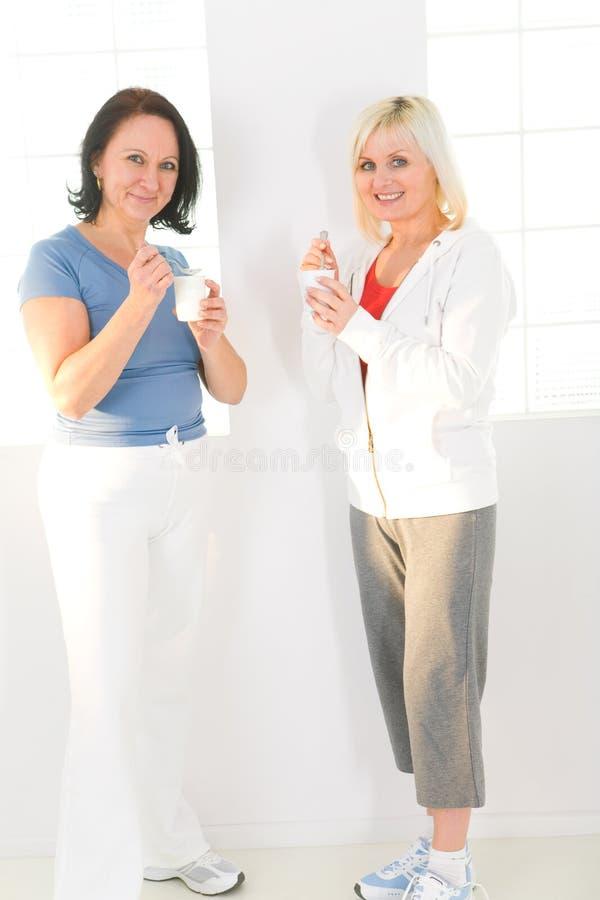 Mujeres que comen el yogur fotos de archivo libres de regalías