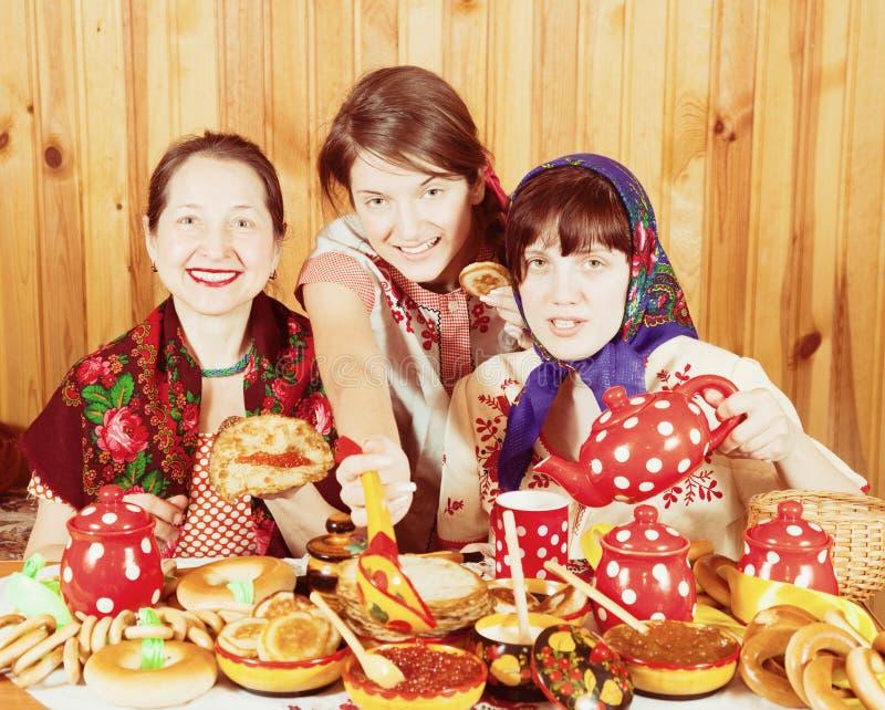 Mujeres que comen la crepe con el caviar durante Shrovetide fotos de archivo libres de regalías