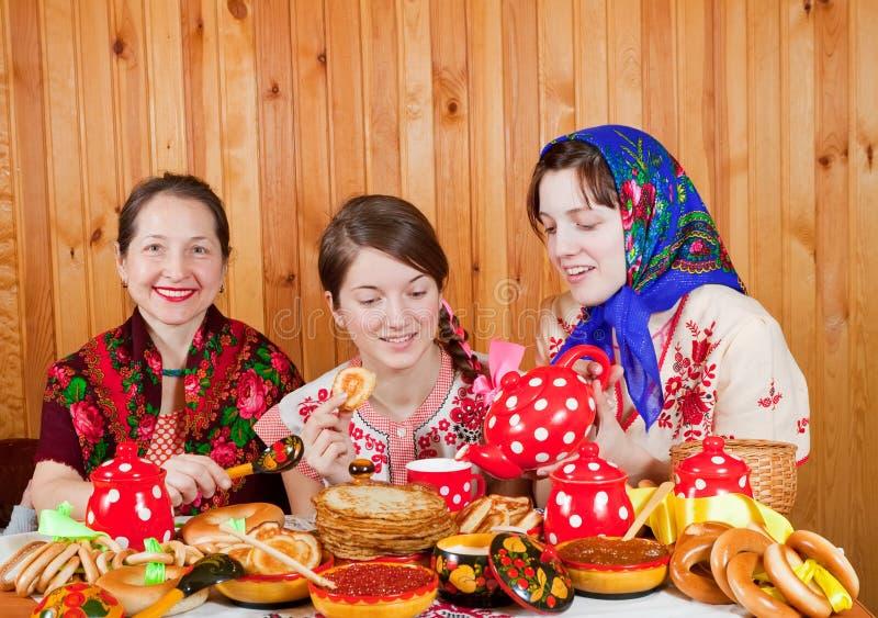 Mujeres que comen la crepe durante Shrovetide imagen de archivo