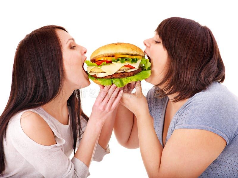 Mujeres que comen la hamburguesa. fotografía de archivo