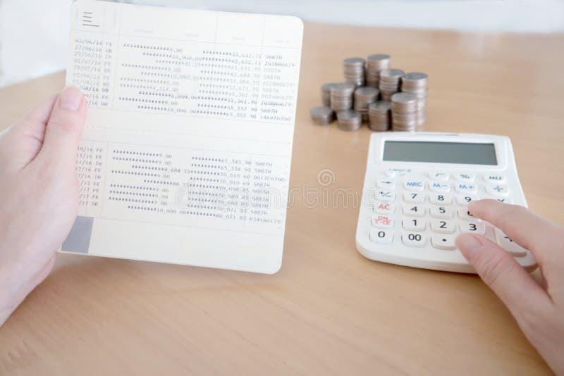 Mujeres que comprueban cantidad en libreta de banco de la cuenta bancaria imagenes de archivo