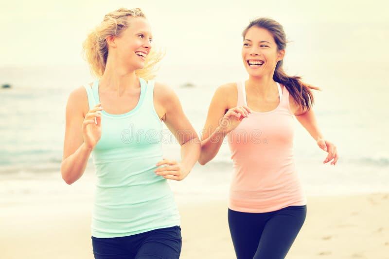 Mujeres que corren ejercitando activar feliz en la playa fotos de archivo libres de regalías