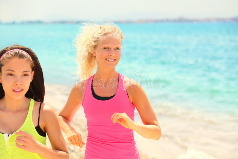 Mujeres que corren la aptitud que activa en la playa del verano imagen de archivo libre de regalías