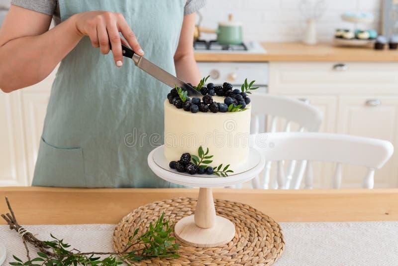 Mujeres que cortan la torta de cumpleaños con las bayas Cierre para arriba Torta blanca con el queso cremoso y ar?ndanos y zarzam imagen de archivo libre de regalías