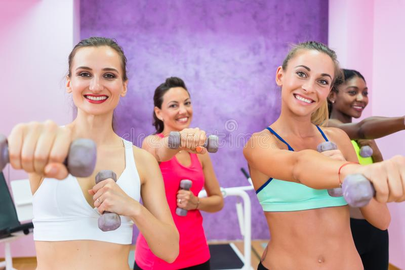 Mujeres que ejercitan con pesas de gimnasia durante clase del grupo en un contempo fotos de archivo libres de regalías