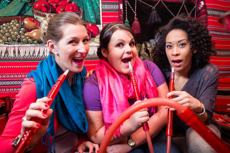Mujeres que gozan de la cachimba o del shisha en café oriental fotos de archivo libres de regalías